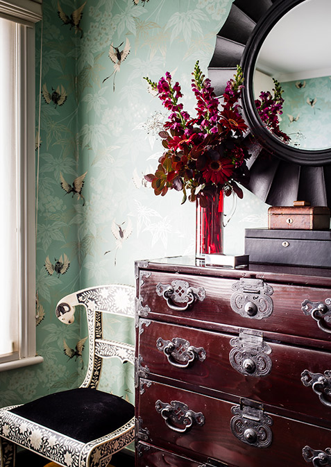 Bedroom with floral bird wallpaper and drawer cabinet