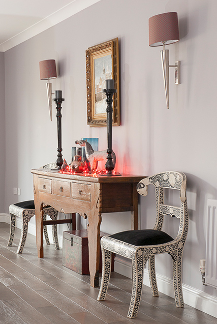 detailed chairs next to table with draws and light decoration in living room