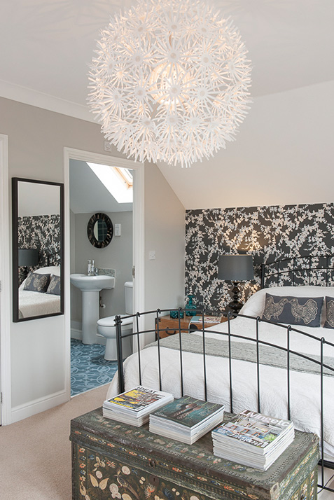 Guest bedroom with feature wall and hanging floral ceiling light