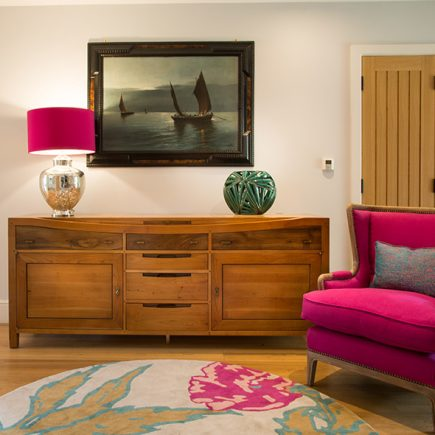 Entrance hall sideboard and bright pink arm chair and lamp