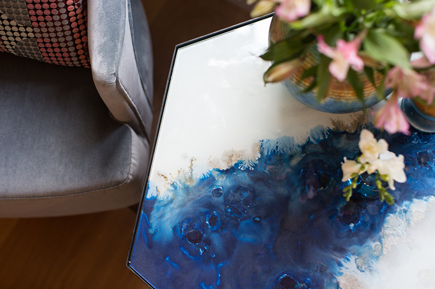 beauiful blue coffee table pattern with flowers on next to armchair