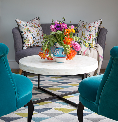 dining room teal arm chairs and bright abstract cushions