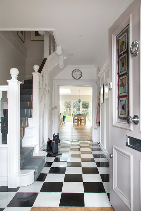 black and white entrance hallway with tiled checkerboard floor