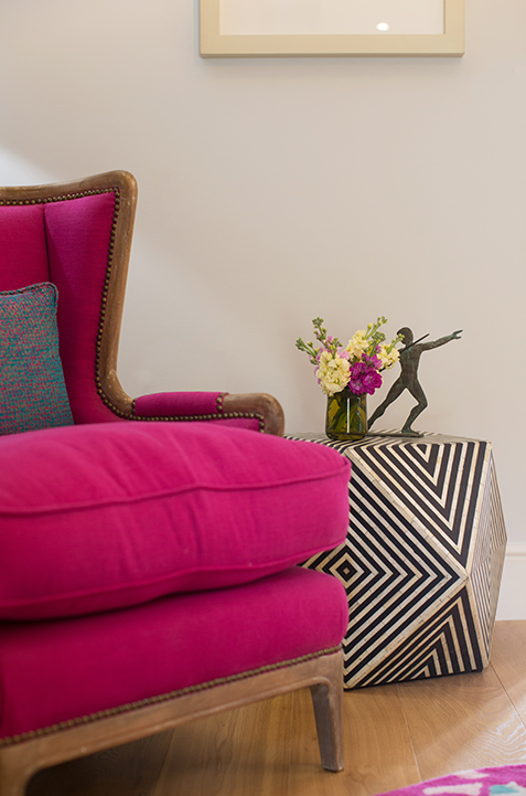 living room bright pink arm chair and geometric side table