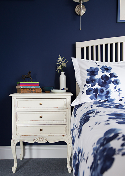 pile of books on bed side table next to white bedding with dark ink blue flower detailing