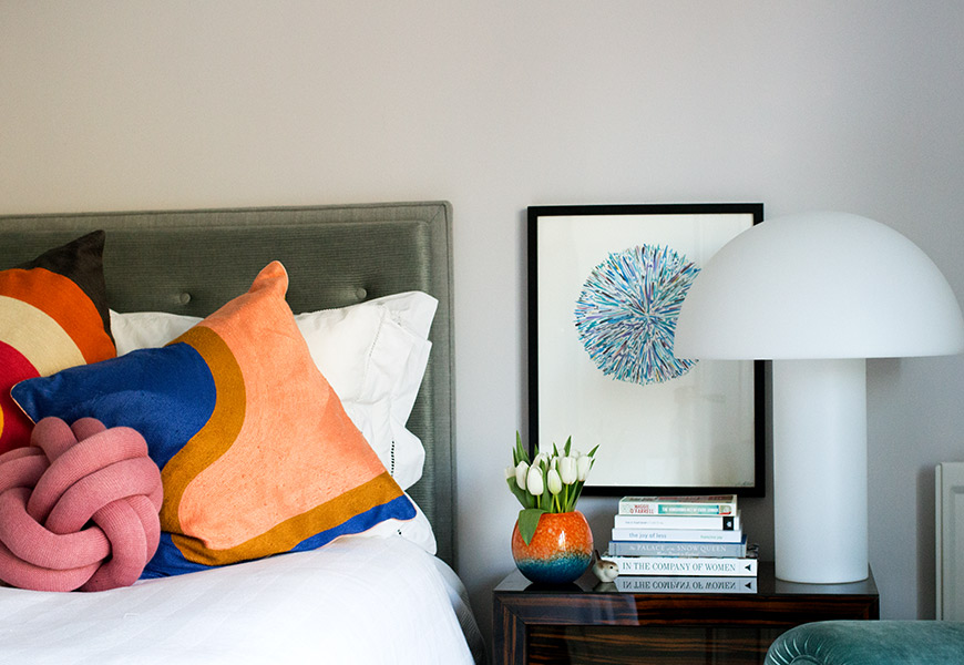 Habitat lamp on side table with books and flowers next to master bed with knot cushion
