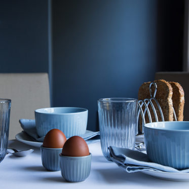 Hammershøi Tumblers in Indigo, Hammershøi Bowls in Sky Blue and Hammershøi Egg Cups in Marble on breakfast table with eggs and toast