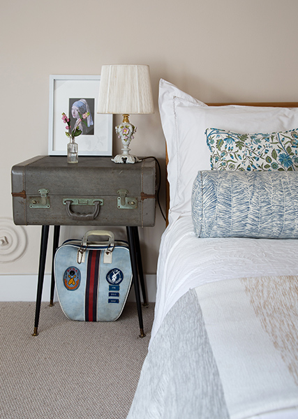 girl with a pearl earring picture frame and soft bedside lamp on suitcase side table