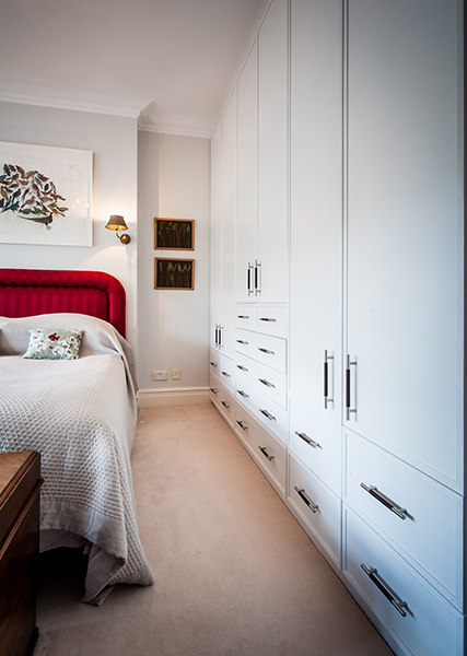 wall to wall white wardrobe in open light bedroom