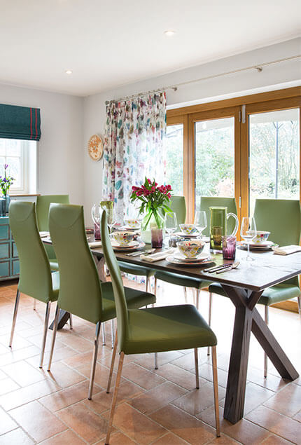 green chairs around light and airy dinning table