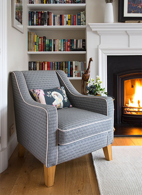 grey armchair infront of a bookshelf and fire in sitting room