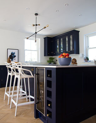 kitchen with white bar stools and navy blue kitchen island