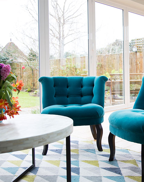 blue velvet arm chairs against bifold doors