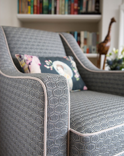 grey embroided armchair infront of book shelf