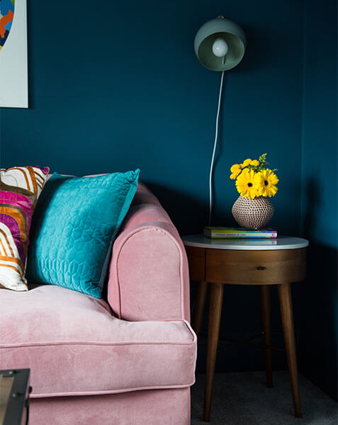 pink velvet sofa against teal walls and modern bedside table