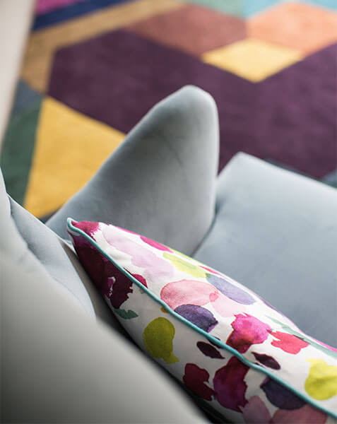 grey armchair with colourful cushion and rub