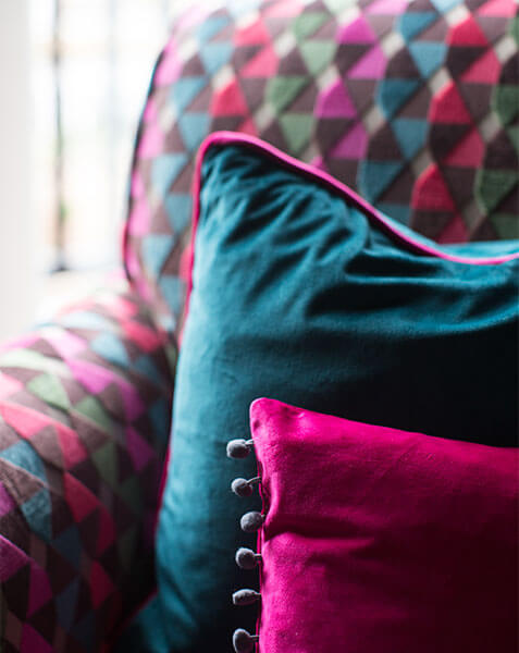 colourful velvet armchair with velvet cushions