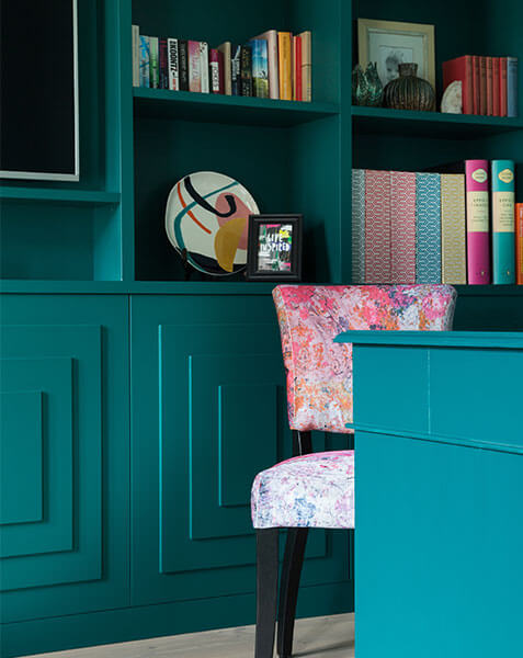 colourful mordern chair behind teal wooden desk