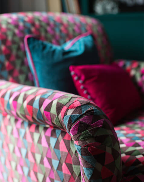 colourful velvet armchair with velvet teal and pink cushions
