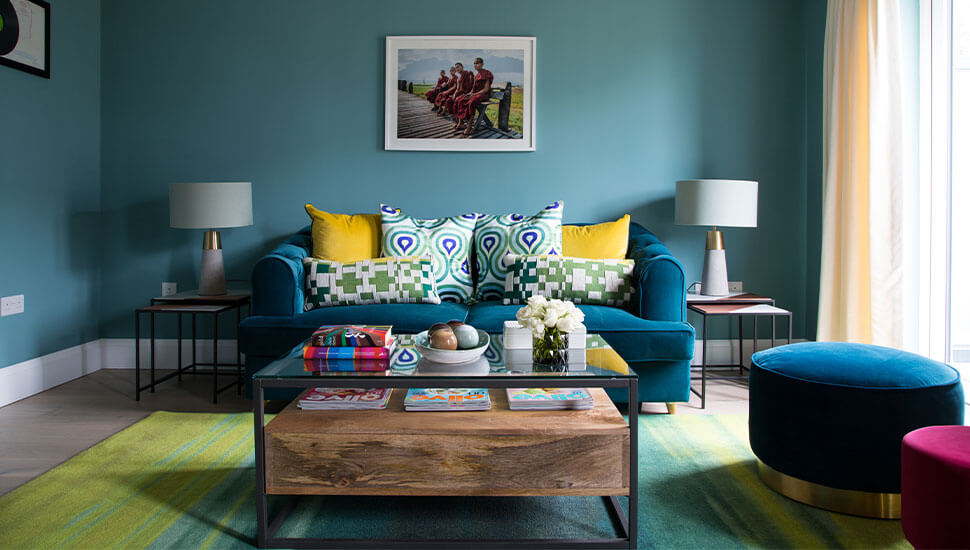 teal sitting room with cosy velvet sofa and pouffes