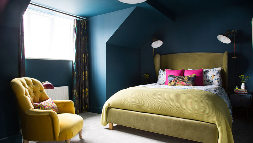 full height curtains against teal walls and yellow furniture