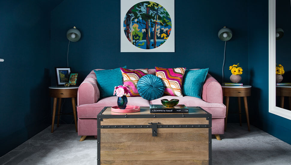 teal room with pale pink velvet sofa and chest coffee table