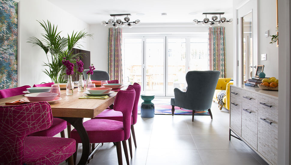pink velvet dinning chairs at wooden table in light kitchen leading to bifold doors
