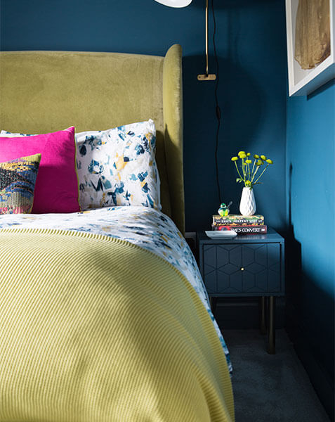 pale yellow master bed against teal walls