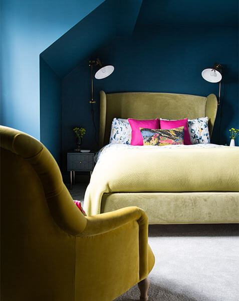 yellow velvet armchair leading to large master bed