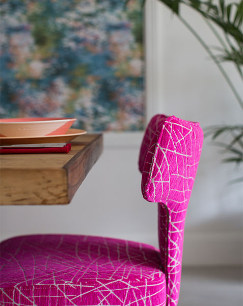 fuchsia pink velvet dining chair at wooden table