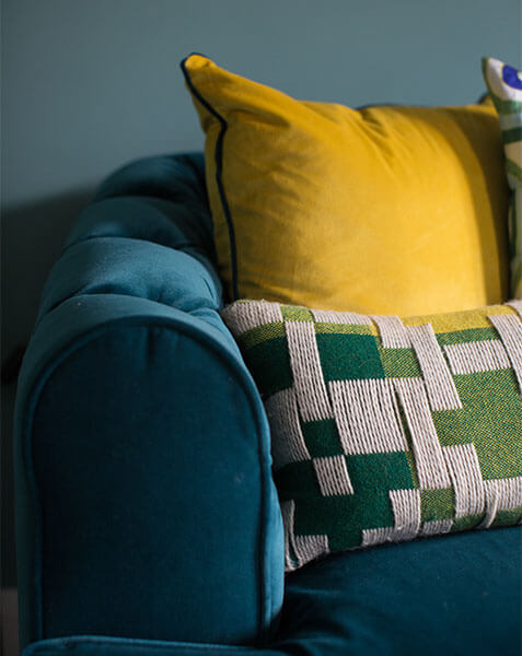yellow and green cushions on teal velvet sofa