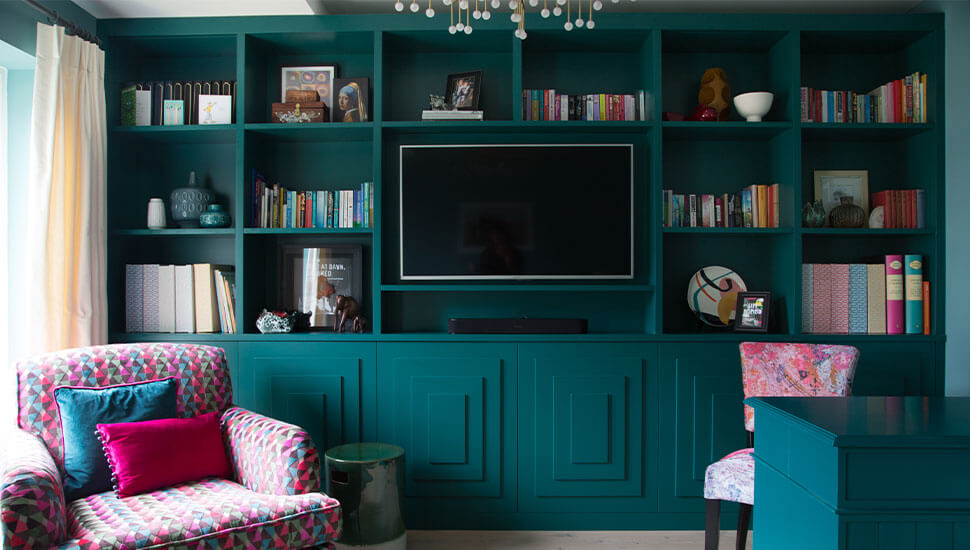 bespoke floor to ceiling teal cabinetry holding TV