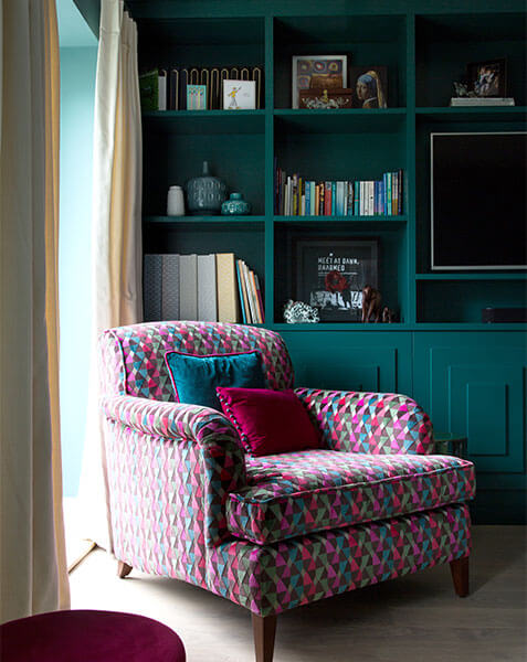 colourful armchair in front of teak cabinets