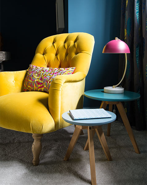 yellow velvet armchair with modern lamp and bedside tables