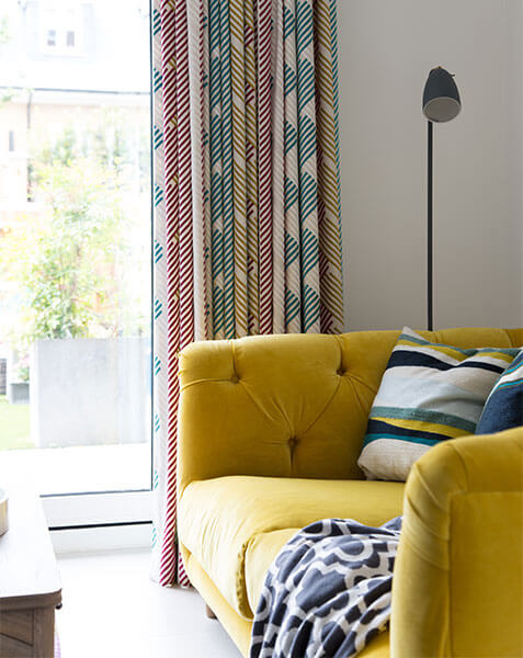 yellow velvet sofa against white wall and pale curtains