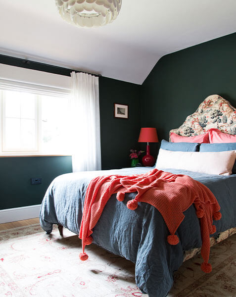 dark walled bedroom with light cosy double bed