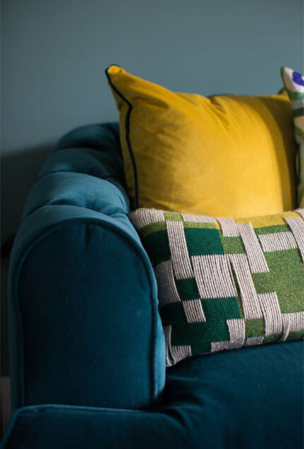 close up teal velvet sofa with yellow and green cushions